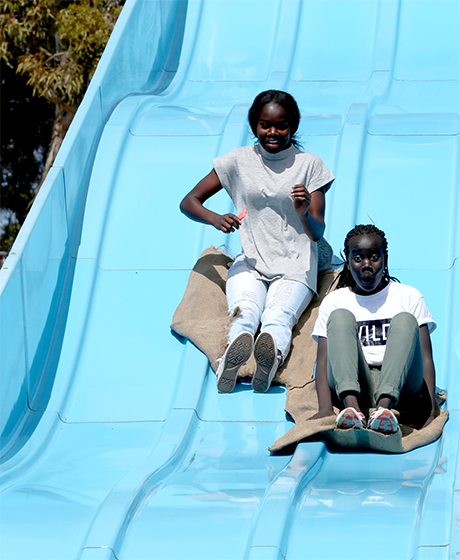 Two girls slide on hessian sacks down a blue slippery slide
