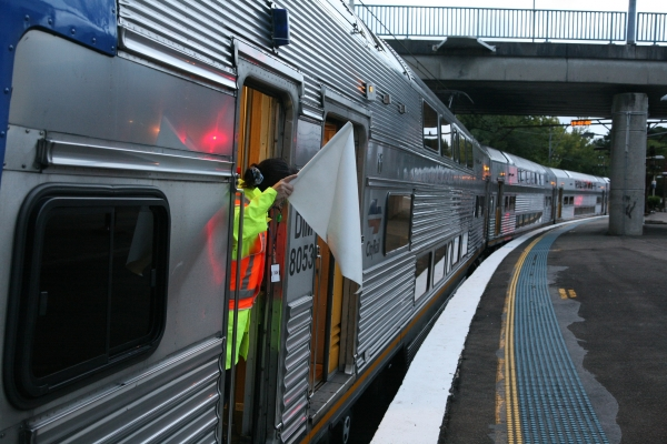 Train conductor waves white flag while train pulls out from platform.