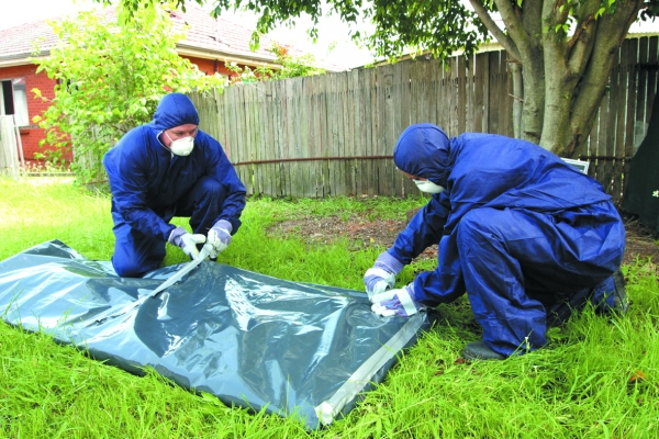 Asbestos removalists wrapping fibro sheet.