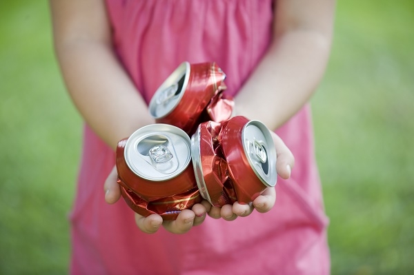 Child holding crushed soft drink cans.